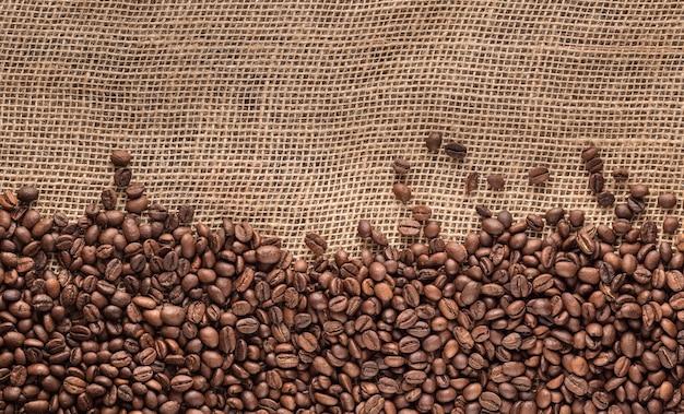 Жареные кофейные зерна, лежащие на мешковине. панорама, место для текста. скопируйте пространство.