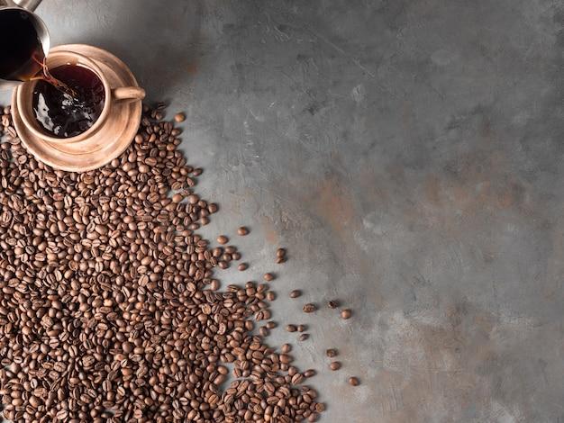 커피 한잔과 함께 회색 벽에 누워 볶은 커피 콩. 상위 뷰, tex에 대한 장소, 복사 공간.