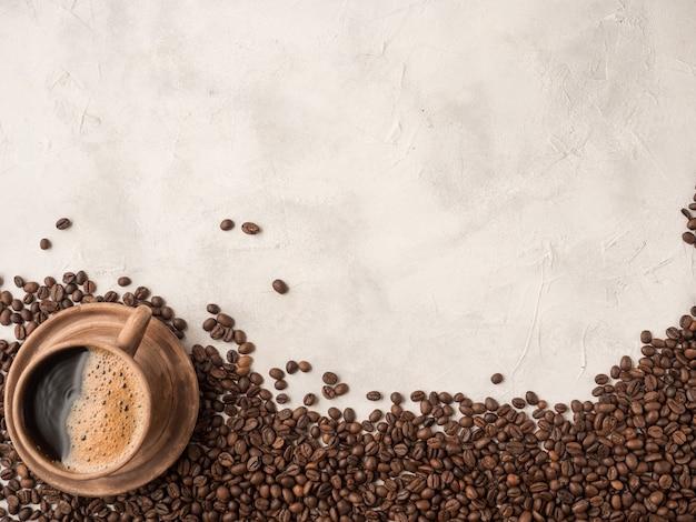 Жареные кофейные зерна, лежащие на белой тарелке с чашкой кофе. вид сверху, место для текс, копировальное пространство.