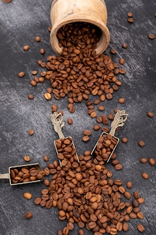 Roasted coffee beans in metal spoon on black surface