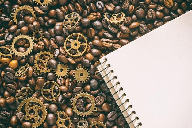 황동 기어와 빈 메모장이 혼합 된 볶은 커피 원두