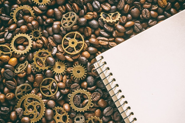 Roasted coffee beans mixed with brass gears and empty notepad