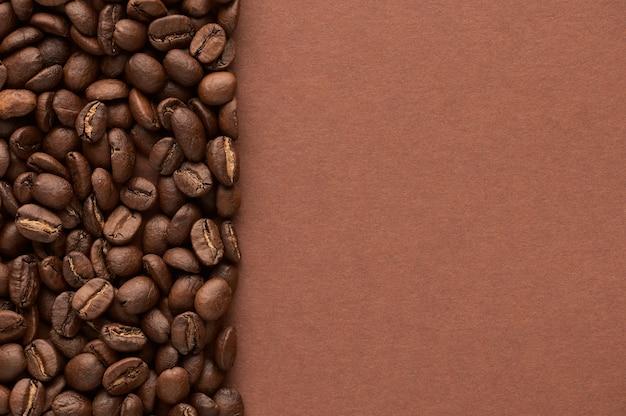 Жареные кофейные зерна на коричневом фоне с копией пространства. крупным планом вид сверху. фото высокого качества