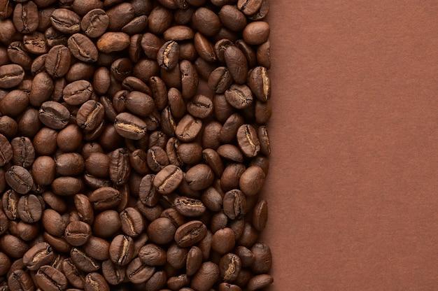 コピースペースと茶色の背景の上の焙煎コーヒー豆は上面図をクローズアップ