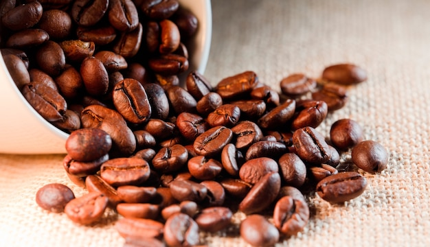Жареные кофейные зерна на ткани из рафии.