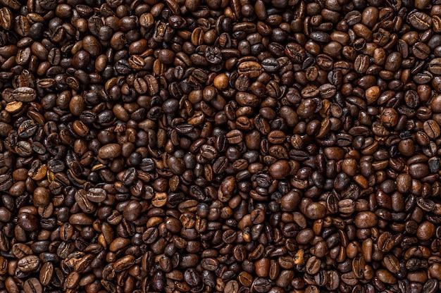Жареные кофейные зерна на деревенском столе.