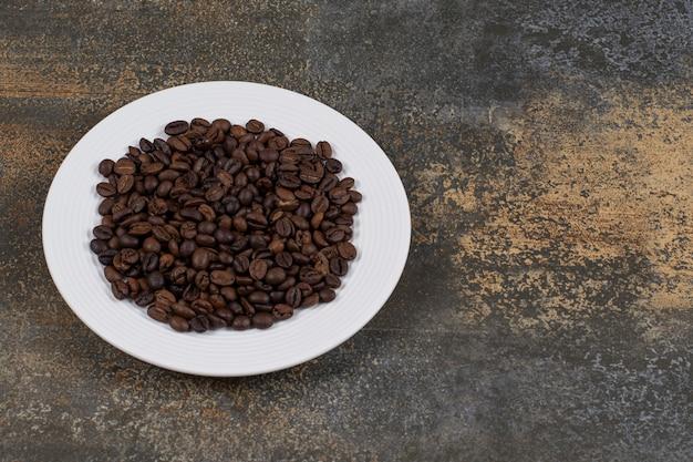 白い皿に焙煎したコーヒー豆。