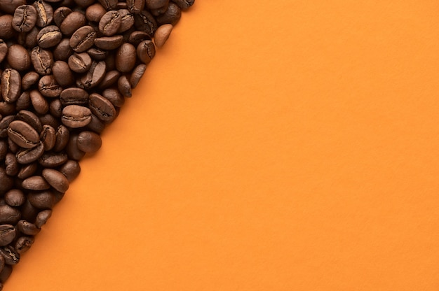 Roasted coffee beans on orange background with copy space. close up top view. high quality photo