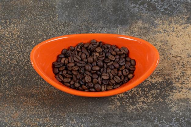 Roasted coffee beans in orange bowl.