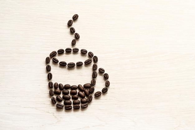 볶은 커피 콩은 텍스트를 위한 흰색 배경 복사 공간에 커피 한 잔의 형태로 놓여 있습니다. 휴식 시간,