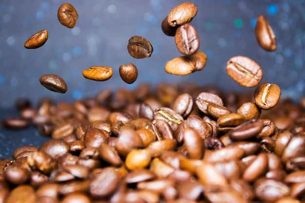 Roasted coffee beans pour from above, hovering in the air on a dark background. side view, close-up