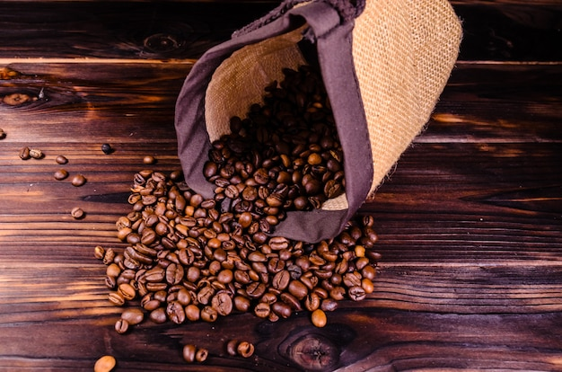 Roasted coffee beans in sack on rustic wooden table