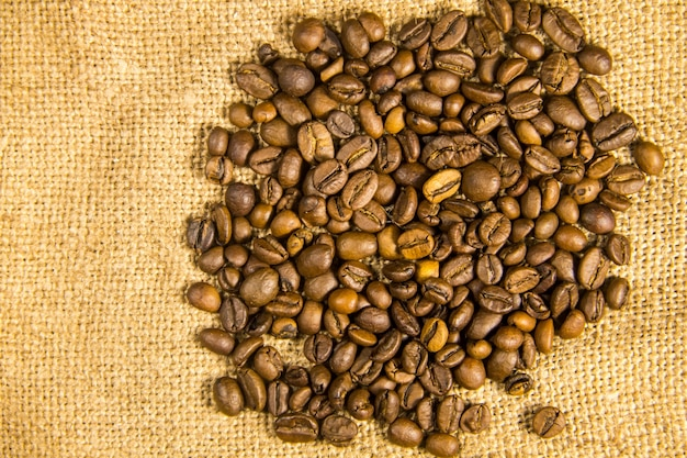 Roasted coffee beans on sackcloth woven background