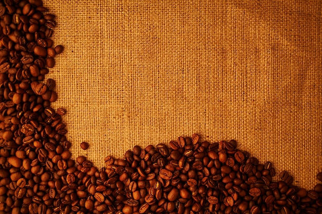 Roasted coffee beans on sacking background