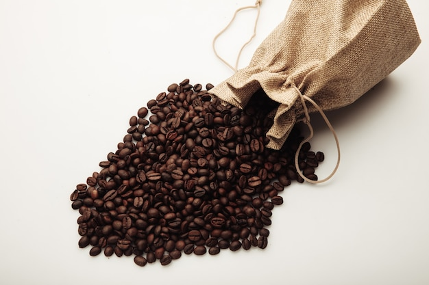 Roasted coffee beans scattered of the bag on white background.