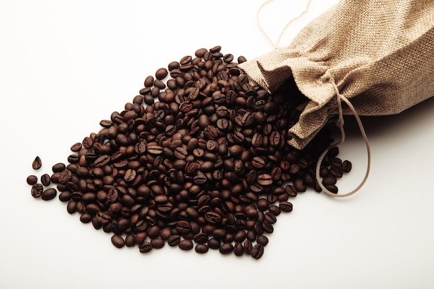 Roasted coffee beans scattered of the burlap bag isolated on white.