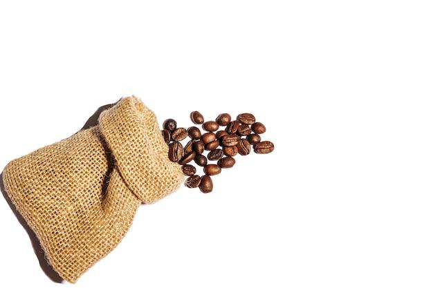 볶은 커피 콩은 흰색 배경에 분리된 삼베 가방에서 흩어져 있습니다. 공간을 복사합니다.