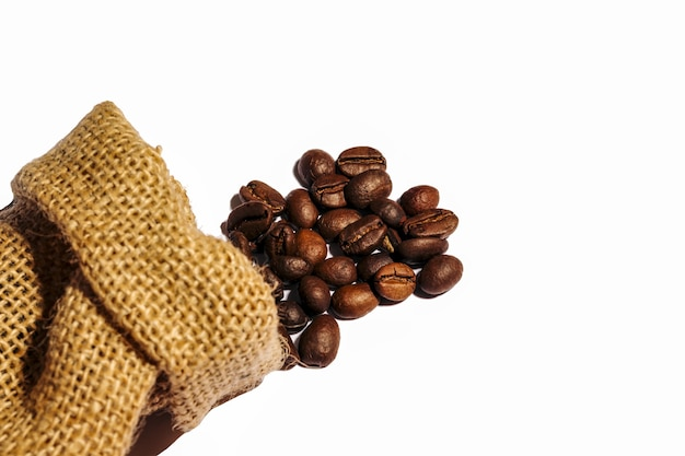 Roasted coffee beans scattered from burlap bag isolated on white background. copy space.