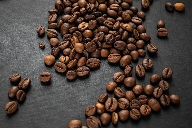 暗い背景に散らばる焙煎コーヒー豆 Premium写真