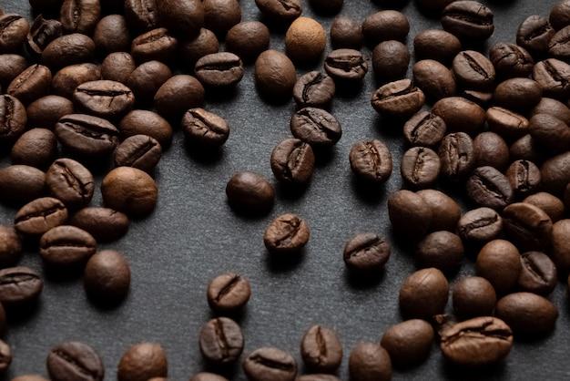 暗い表面に散らばった焙煎コーヒー豆