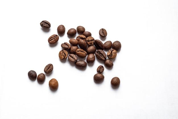 白い表面に散らばった焙煎コーヒー豆