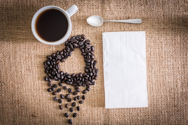 Roasted coffee beans in the shape of a heart and coffee cup, tissue paper. sackcloth is background