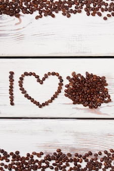 Roasted coffee beans in a shape of letter i and heart. heap of coffee beans on white wood. i love coffee concept.