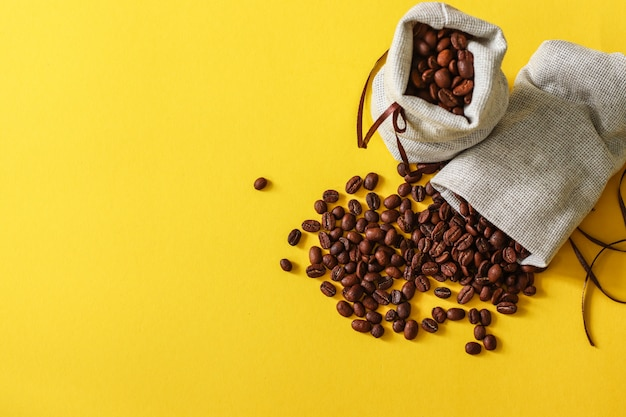 Roasted coffee beans in small sack on yellow background