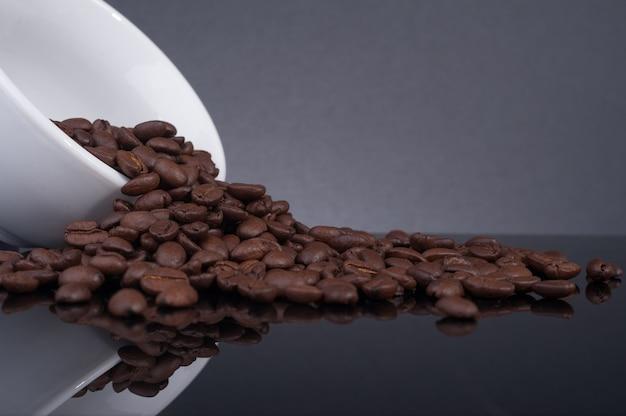 Жареные кофейные зерна выливались из кружки на черном столе с отражением.