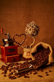 Roasted coffee beans, vintage coffee-mill on sacking background