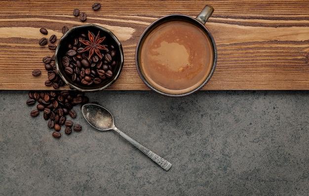 어두운 돌 배경에 커피 컵이 설치된 볶은 커피 콩.
