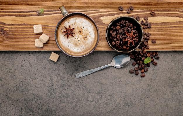 Жареные кофейные зерна с настройкой чашки кофе на темном камне.