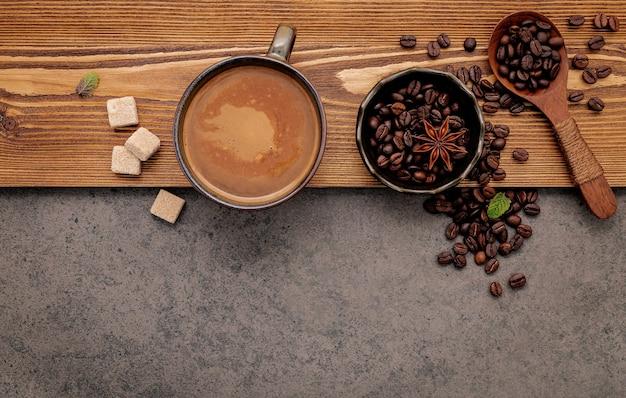 어두운 돌에 커피 컵 설치와 함께 볶은 커피 원두.