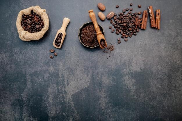 Жареные кофейные зерна с кофейным порошком и ароматными ингредиентами для приготовления вкусного кофе на темном камне.