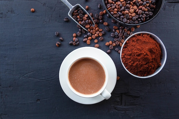 Roasted coffee beans with coffee powder and coffee cups.