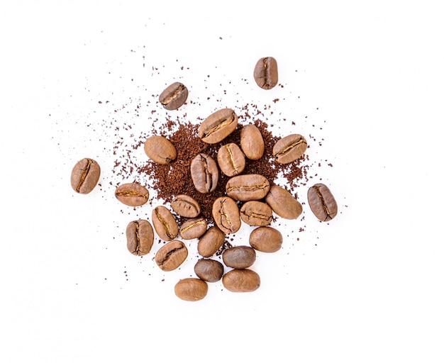Жареные кофейные зерна с молотым кофе на белом фоне
