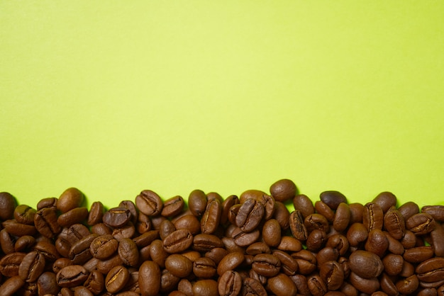 Roasted coffee beans on the yellow background.
