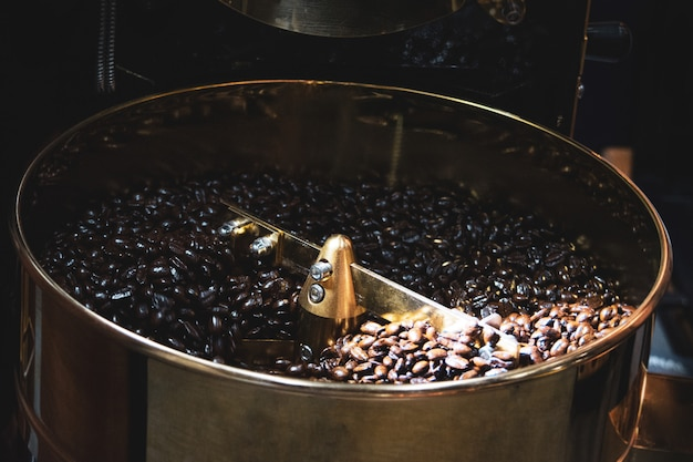 Roasted coffee in coffee roaster, machine for roasting coffee bean roasting close up