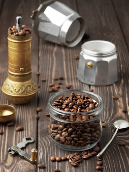 Roasted coffee grains in a glass jar and scattered coffee grains on a wooden brown table