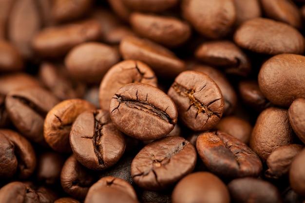 Жареный кофе кофейных зерен текстуры фона, выборочный фокус
