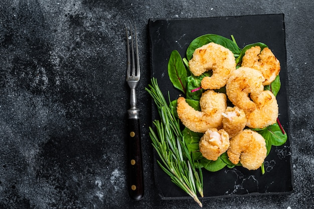 Roasted crispy shrimps  prawns on a marble board with green salad. black background. top view. copy space.