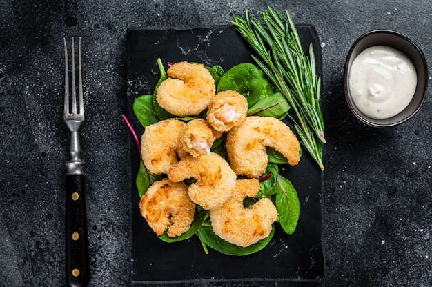 Roasted crispy shrimps  prawns on a marble board with green salad. black background. top view.