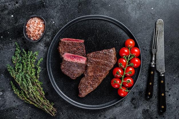 Жареный стейк из говядины порезанный на тарелке с тимьяном. черный фон. вид сверху.