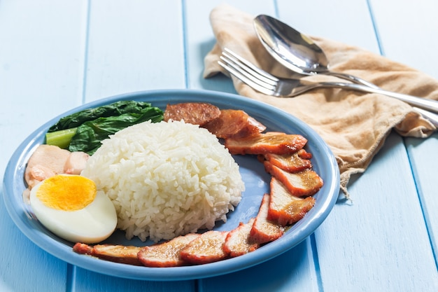 Roasted duck boiled eggs with rice on blue plate served on desk