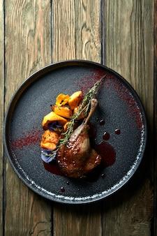 Roasted duck leg with confit pumpkin, closeup.