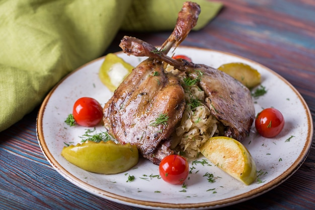 Roasted duck leg with sauerkraut, apple and cherry tomatoes. tasty duck with garnish