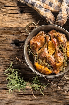 Жареные утиные ножки на сковороде с апельсинами, зеленью, краснокочанной капустой и картофельными лепешками.