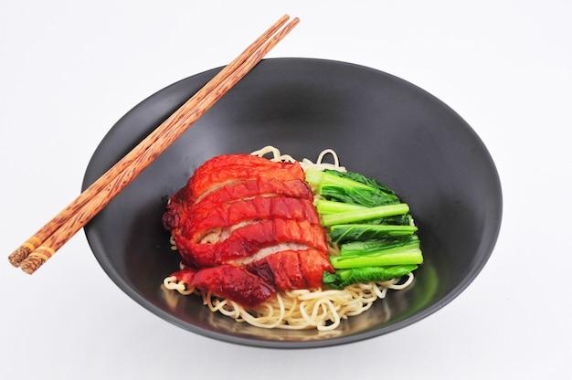 Жареная утиная лапша с соусом китайской кухни на белом фоне