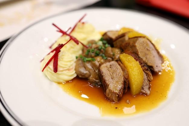 Жареная утка с апельсиновым соусом и картофельным пюре украсьте блюдо аппетитно на белой тарелке в ресторане.
