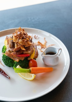 Жареная утка с соусом из приправ и овощами на белой тарелке